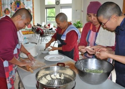 The nuns give a mo-mo transmission to Ruby as they make lunch for the community.