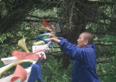 Venerable Chonzum braves a rainy windy day to hang prayers flags at <br> Sukhavati.