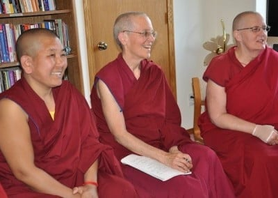 The joys of community bring smiles to Venerables Chonzum, Semkye, and Jigme as they sit together and share.
