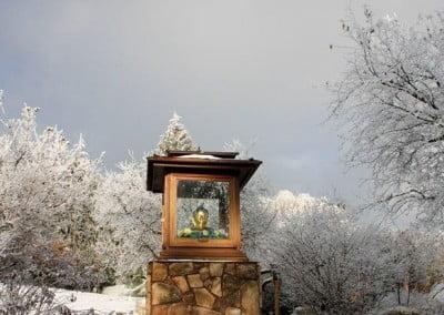 A Buddha shrine in a snow covered garden