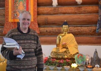 A man stands next to a Buddha statue