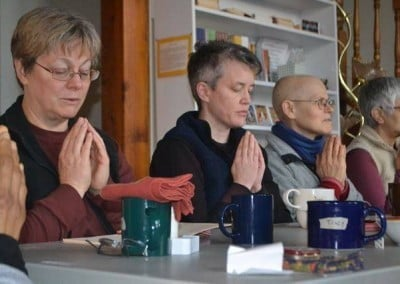 A group of people sitting at a table with hands in prayer