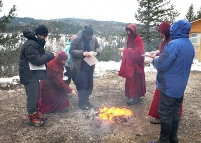 People throw sesame seeds into a fire