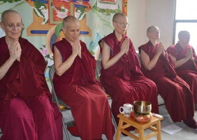 A group of Buddhist nuns with hands in prayer
