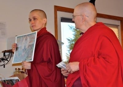 Venerable Jampa holds up a picture of Chenrezig that she and Venerable Jigme will offer to a guest retreatant.
