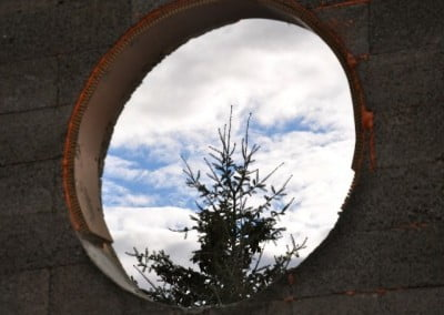Looking through one of the round openings that will eventually hold a lovely stained glass window, you now see a lovely Doug fir tree.