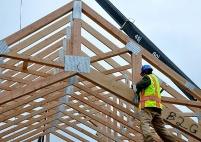 George nails large hangers onto some of the trusses where other trusses will then be placed perpendicular to them.