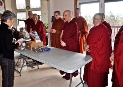 Sarah Conover makes a food offering and shares in a prayer of <br> interdependence with the sangha.