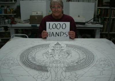 "Bev poses with the drawing and a sign that says ""1000 Hands"""
