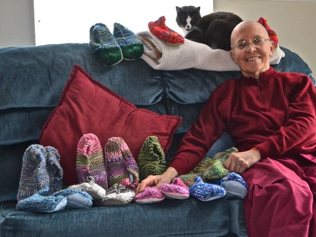 Venerable Thubten Semkye and Maitri pose with hand-knitted slippers made by Susan Durick for the Y.E.S. teens in Newport.