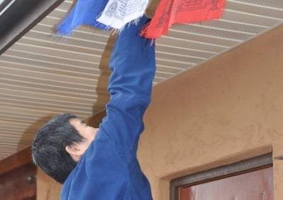 A woman hangs prayer flags