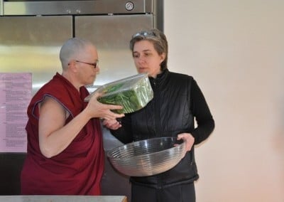 A buddhist nun, Venerable Yeshe holding a plastic box with salad leaves, another woman holding a large glass bowl in her hand.