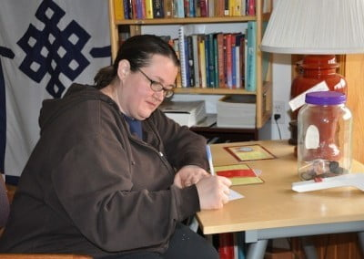 A woman writing a thank you card to the Abbey community.