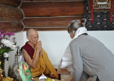 A woman making an offering to Venerable Chodron.