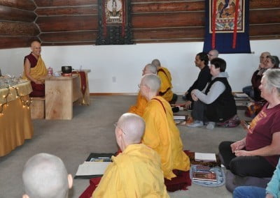 Buddhist nuns and a group of people listening to Venerable Chodron in the meditation hall
