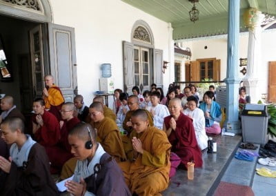 Buddhist nuns from three traditions and lay people sitting on the floor with hands praying.