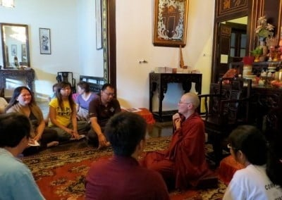 Venerable Chonyi sitting on the floor with the lay retreatants.