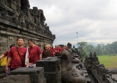 Many people and some buddhist nuns circumabulating the stupa.