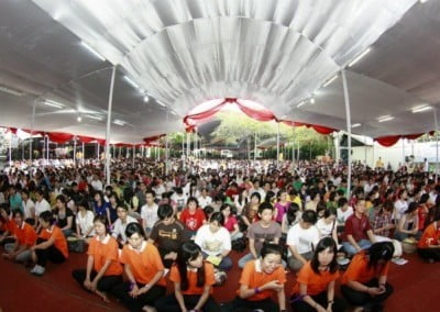 Many people sitting on the floor in a tent celebrating vesak day in Jakarta.