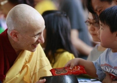 Venerable Chodron smiling happily at a small boy who is offering alms to her.
