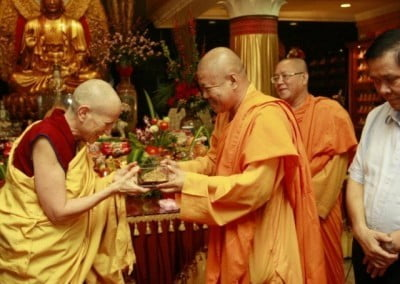 A buddhist monk, Ekayana abbot and vice abbot giving Venerable Chodron a gift, a replica of Borobudur.