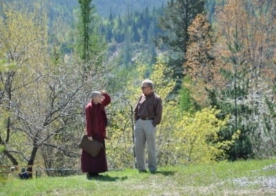 Venerable Samten talking to a man in front of a grove of blossoming trees.