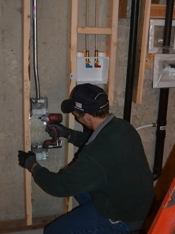 Sean installs one of the many dozens of electrical outlets placed throughout the hall.