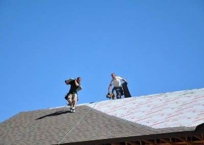 Closeup of two roofers working diligently on the Chenrezig Hall roof.