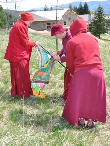 Venerables Chodron, Jampa, and Semkye attach a lovely Tara prayer flag donated by the Tibetan Center in Hamburg.
