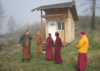 Tan Khemako and Ajahn Jotipalo show the Abbey sangha a kuti—a meditation hut—on the hermitage property.