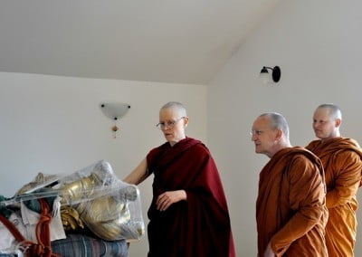 Venerable Thubten Tarpa shows Ajahns Passano and Jotipalo the inside of the Kuan Yin statue, which is being prepared for filling.