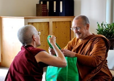 Venerable Thubten Semkye makes an offering of health food items to Ajahn on behalf of the Abbey community.