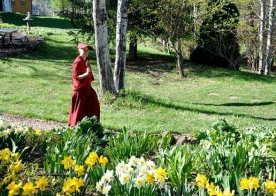 Venerable Thubten Jampa enjoys walking with a small prayer wheel in the garden.