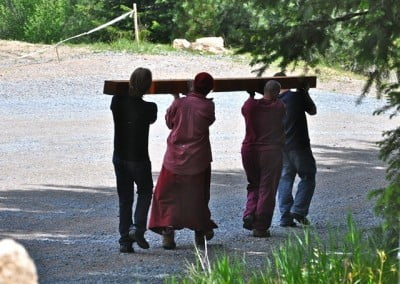 Venerable Thubten Tarpa gets lots of help to move large beams to the barn.