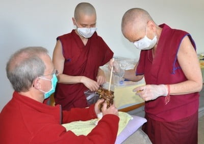 Ken holds one of the smaller statues while Venerable Thubten Chodron fills it.
