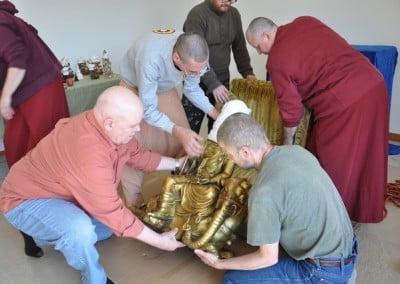Setting the Kuan Yin statue gently on a platform.