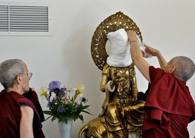 Venerable Thubten Chodron uncovers the face.