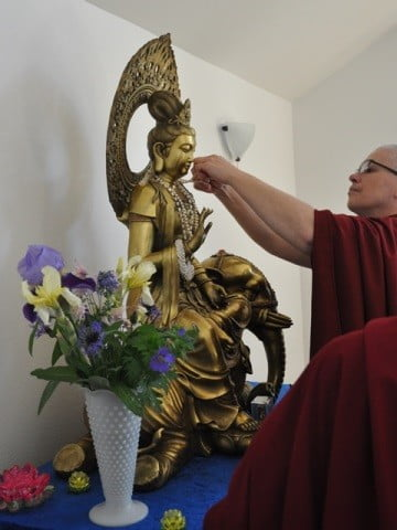 Venerable Thubten Yeshe offers a pearl necklace.