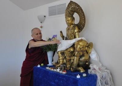 Venerable Thubten Chodron placing the Khata on Kuan Yin's lap.