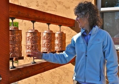 Nancy creates merit by turning the prayer wheels.
