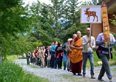 A procession of lay and monastics walk towards the meditation hall.
