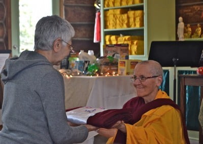 A lay person offers a robe to Venerable Semkye