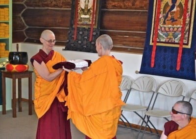 Venerable Samten, the karman master, presents the robe of merit to the robe keeper, Venerable Chonyi.