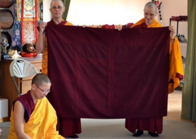 Venerable Chonyi gets help from Venerable Jampa to display the robe to the bhikshuni sangha.