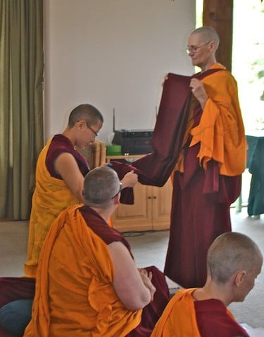 Venerable Chonyi offers the merit robe to Venerable Damcho