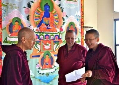 Three nuns talk in front of a Medicine Buddha print.