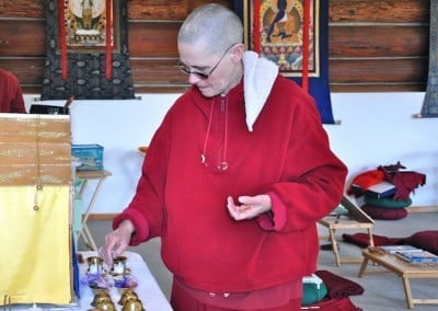 Venerable Chonyi places light offerings on the altar.