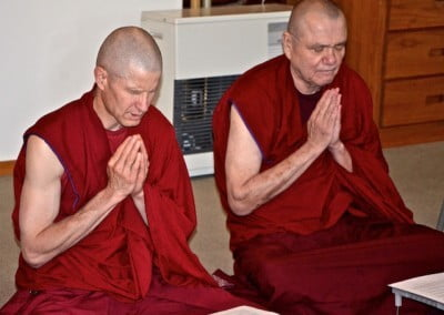 Two monks with hands folded, chanting