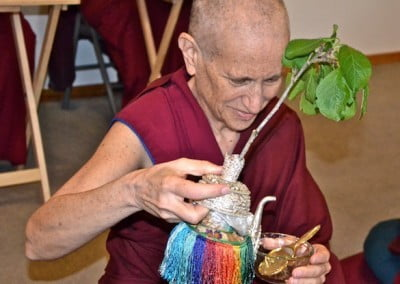 Venerable Chodron offers a bath to Chenrezig.