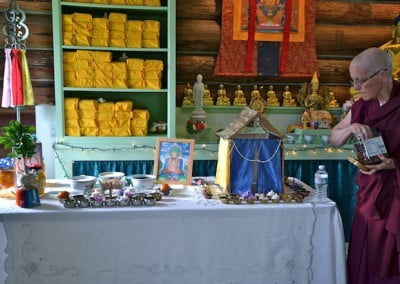 A table full of food offerings sits before the shrine.